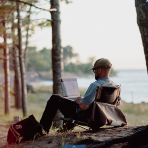 A person works on a laptop in front of a lake.